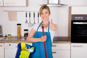 ○ Blonde cleaning lady smiling and holding cleaning supplies