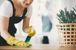 ○ Cleaning lady wiping down table with yellow cloth