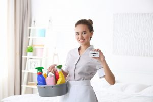 Housekeeper holding up business card that says contact us