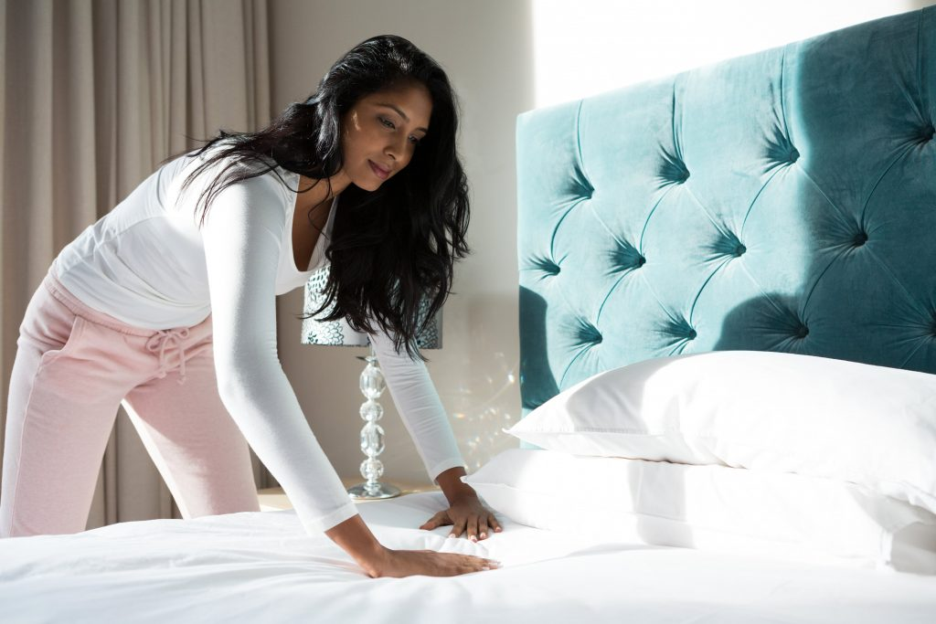 Woman making bed at her home
